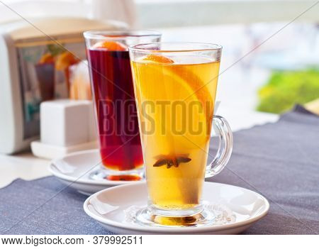 Mulled Wine In Tall Glasses In A Cafe. Warming Drink With Fruits And Spices.