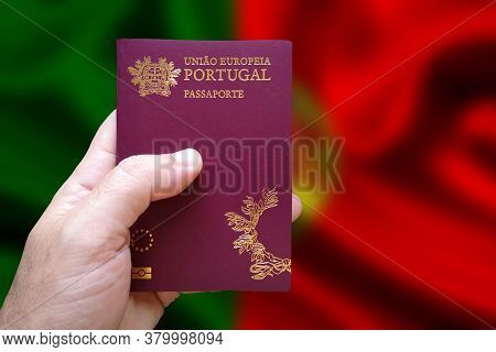 Man's Hand Holding Portuguese Passport With Defocused Portuguese Flag In The Background. Written In