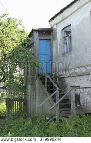 An Old Abandoned European Home With A Wooden Blue Door With A Closed Lock, Wooden Staircase And An U