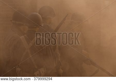American Soldiers In World War Two Uniform, Covered By Smoke And Ready To Enter The Battlefield