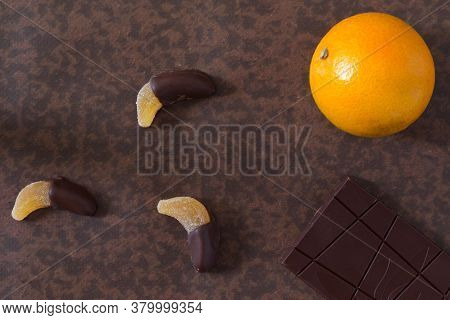 Fruit Candy Dipped In Chocolate, Together With A Chocolate Bar And An Orange.
