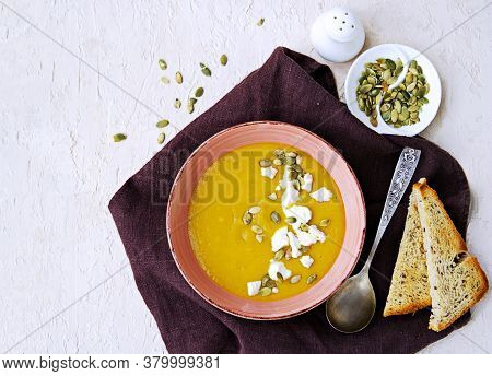 Pumpkin Puree Soup In A Pink Clay Bowl On A Light Concrete Background. Served With Feta Cheese, Pump