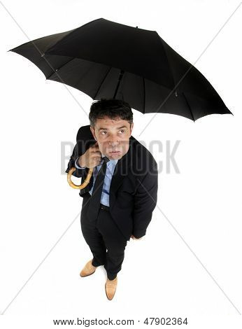 Humorous high angle full length portrait of of a morose businessman eying the weather standing under his umbrella looking up with a petulant expression, isolated on white