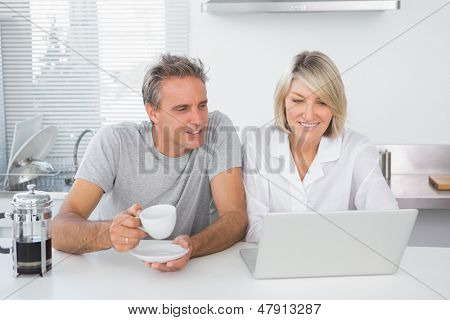 Happy couple using laptop in the morning sitting at kitchen counter