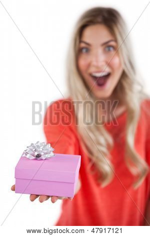 Astonished woman holding a gift on a white background