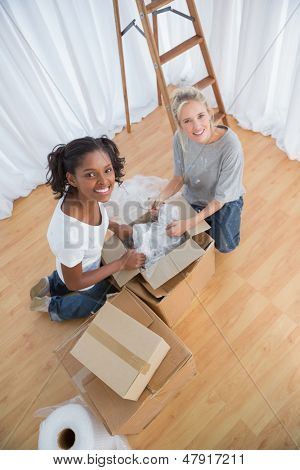 Pretty housemates unpacking boxes in new home and smiling at camera
