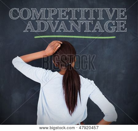 Woman looking at the word competitive advantage written on a chalkboard