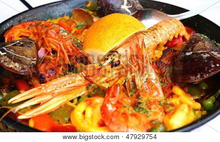 Spanish paella with seafood in a pan - close up poster