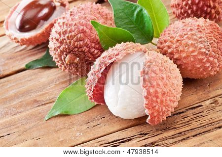 Lychee with leaves on a wooden table.