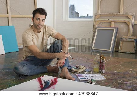 Portrait of a male artist sitting with painting tools on floor at a studio