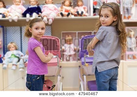 MOSCOW - MAR 18: Anya 7 years old and Jeanette 6 years old with a rows of dolls  purchased a buggy in a childrens store Jakimanka on March 18, 2012 in Moscow, Russia.