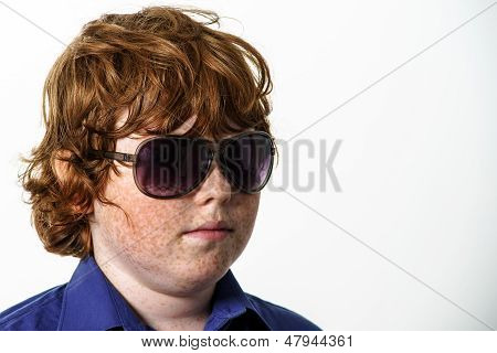Freckled red-hair boy with glasses showing boss. Isolated on white background. poster