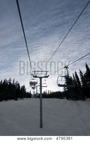 Chair Lift At Ski Resort With Silhouetted Skiers