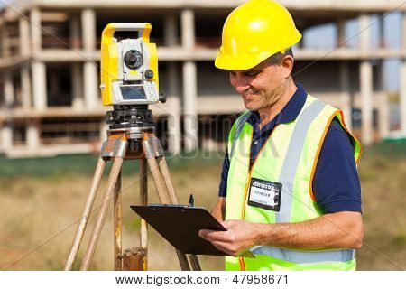 mid age land surveyor working at construction site with theodolite