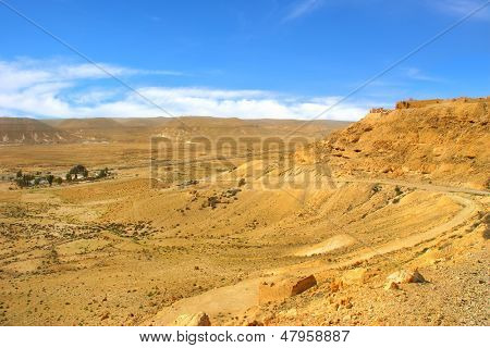 View of dusty road runs along rocky slop and valley under beautiful blue sky with white clouds at Negev desert in Israel.