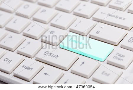 Close Up Of White Keyboard  With Glowing Blue Enter Button