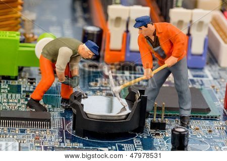 a worker repairs the motherboard of a computer. symbolic photo for data security