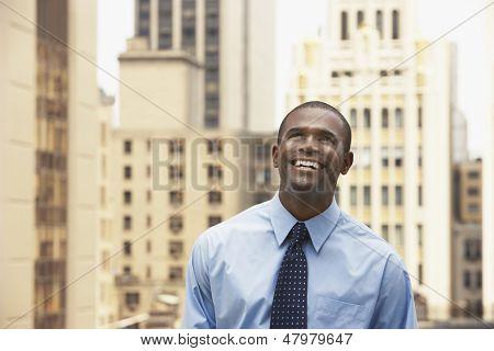 Happy African American businessman looking up against office buildings