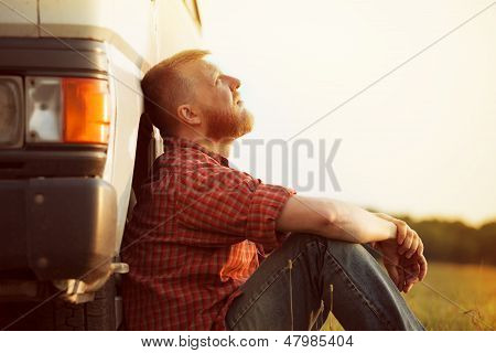 Bearded truck driver takes a break from work poster