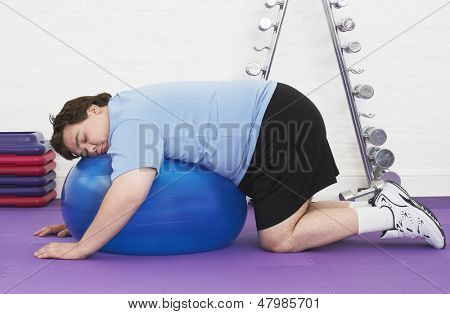 Side view of an overweight man sleeping on exercise ball in health club