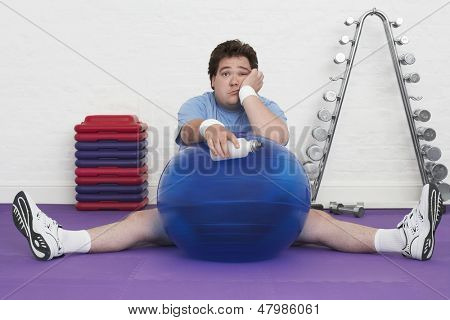 Portrait of a tired overweight man sitting on floor with exercise ball in health club