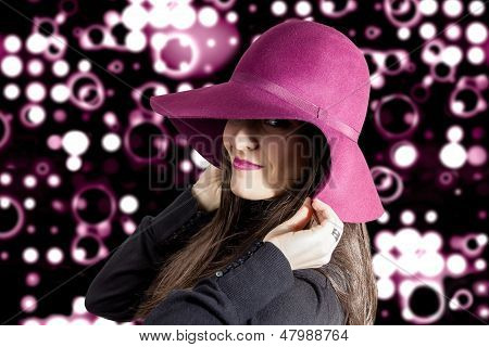 Portrait of beautiful young girl with a garnet hat on her head in front of spotlights background poster