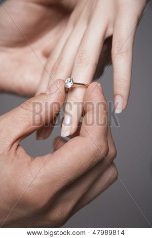 Closeup of man placing engagement ring in woman's finger against gray background
