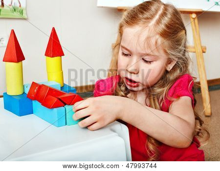 Child preschooler play wood block in play room. Child care.