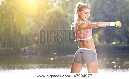 female fitness instructor exercising with small weights in green park