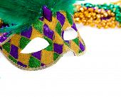 A purple, gold and green mardi gras mask and beads on white poster