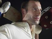 Closeup of a cricket player holding cricket bat behind shoulders against black background poster