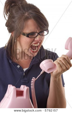Young angry woman yells into the telephone; isolated on white