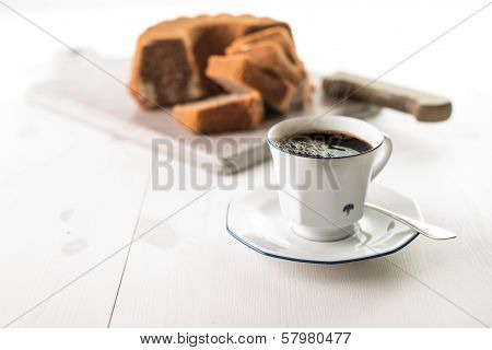 Coffee Cup On A White Wood Table With Cake In The Background