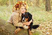 happy smiling mature woman with dog sitting near tree looks at camera poster