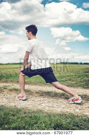 Man limbering up before exercise stretching his leg muscles to increase mobility as he stands on a track in a rural field , side view