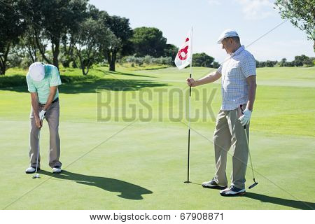 Golfer holding eighteenth hole flag for friend putting ball on a sunny day at the golf course