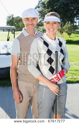 Happy golfing couple looking at camera with golf buggy behind on a sunny day at the golf course