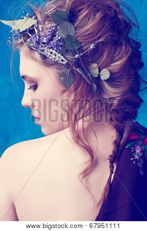 portrait of a beautiful woman with red hair in curly braided hairstyle wearing a crown of fresh flowers