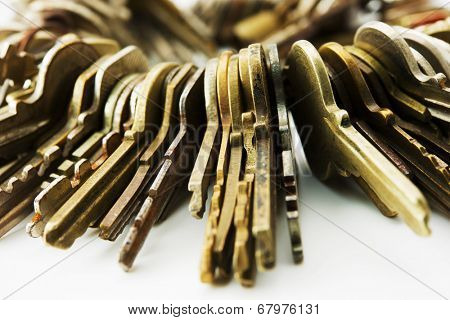 Many brass and chrome old keys on white table. Security and encryption, concept image. poster
