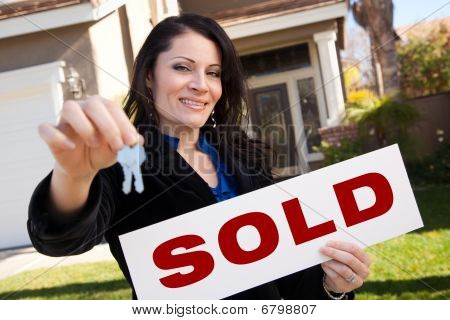 Hispanic Woman Holding Keys And Sold Sign In Front Of House