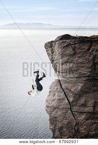 businessman fall from cliff sea background