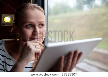 Smiling young woman traveling by train