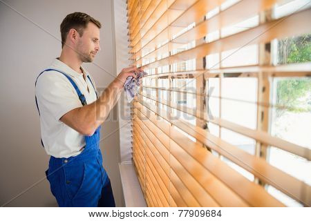 Handyman cleaning blinds with a towel in a new house