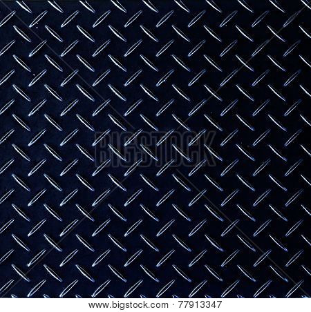 Texture of a dark metal diamond pattern plate.