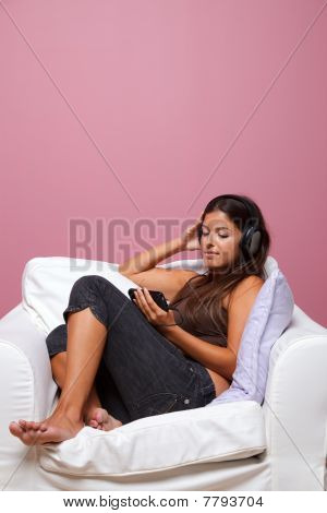 Woman Sat In An Armchair Listening To Music