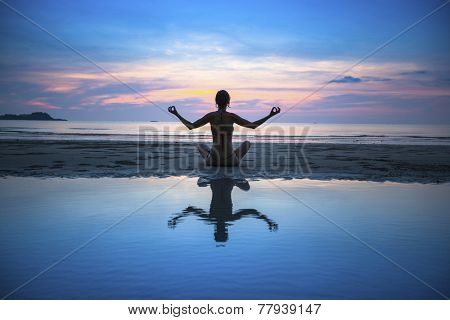 Silhouette of yoga woman meditating on the ocean beach. Yoga and fitness.