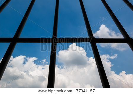 View trough windows of prison and blue sky background