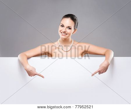 Portrait of young, beautiful and healthy woman in a pearl necklace and with a blank banner