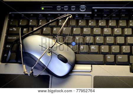 Computer Mouse With Glasses On Keyboard