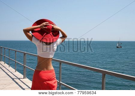 Girl in a red hat on sea